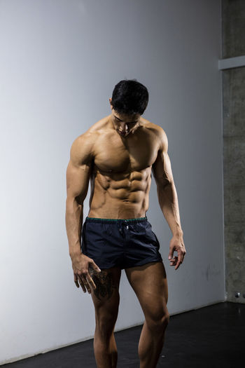 Muscular male fitness model posing behind a grey wall. Adult Asian  Athlete Body & Fitness Human Body Long Shot Man Nam Vo Shirtless Sportsman Abs Fitness Model Grey Wall Handsome Head Down Hunk Looking Away From Camera Male Muscle Muscular Build One Person Shorts Strong Studio Shot Torso