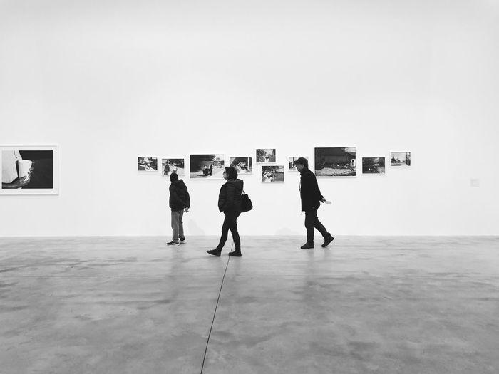 Rear view of people walking on tiled floor against sky