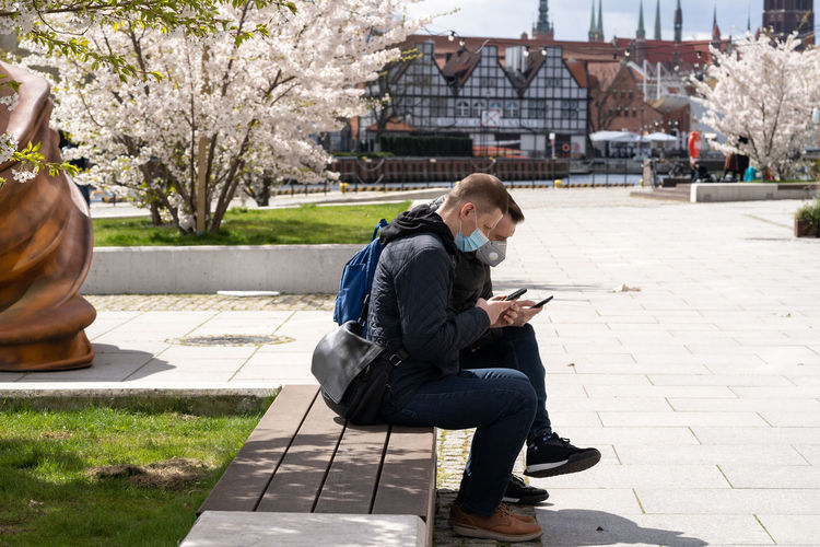 Full length of man using mobile phone while sitting outdoors