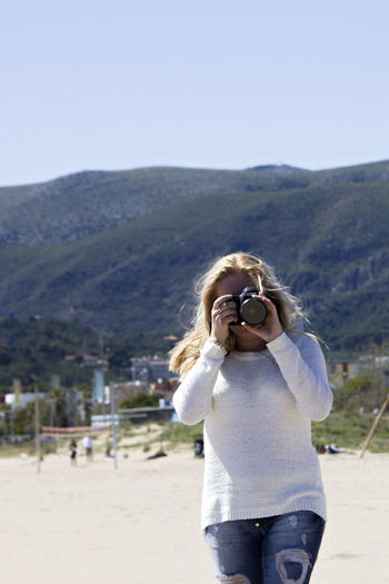 People snapping photos Beach Photography Beauty In Nature Blonde Girl Casual Clothing Day Focus On Foreground Girl Landscape Leisure Activity Lifestyles Make Picture Making Photos Mountain Mountain Range Nature Outdoors People Photography Photographer Photography Sea Seaside Sky Snapping Pics Snapping Pictures Spring