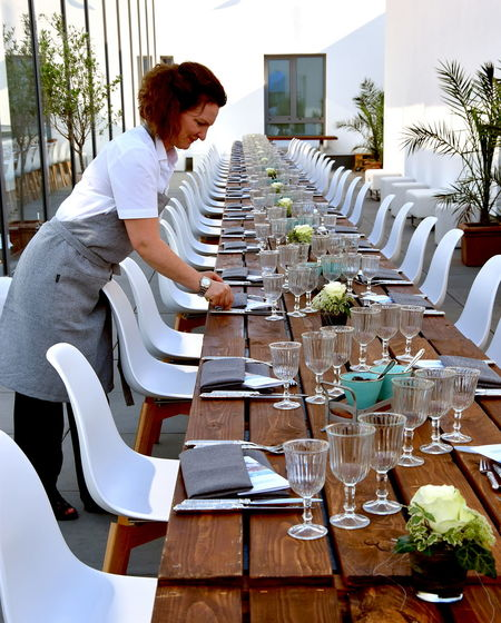 Woman setting table in restaurant