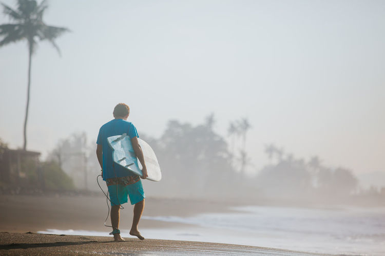 Rear view of man with surfboard walking at beach against sky