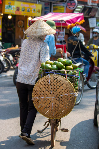 Rear view of woman with umbrella at market stall in city