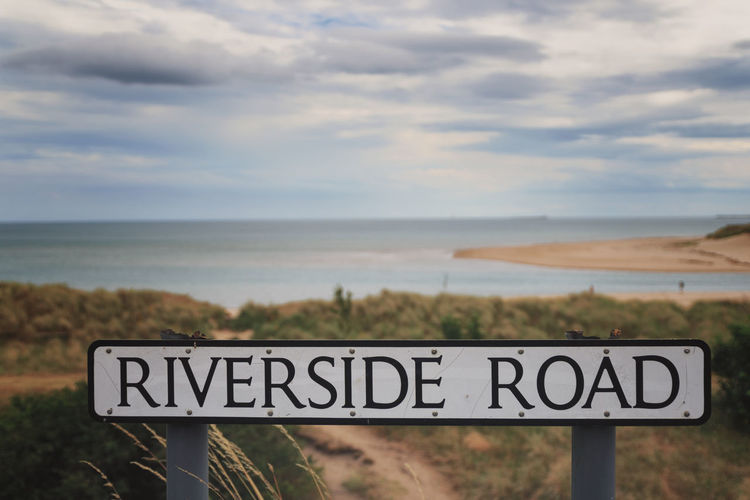 Riverside Road Alnmouth Northumberland Text Communication Western Script Sky Cloud - Sky Water Sign Horizon Sea No People Nature Scenics - Nature Beauty In Nature Day Information Land Horizon Over Water Tranquility Focus On Foreground Outdoors