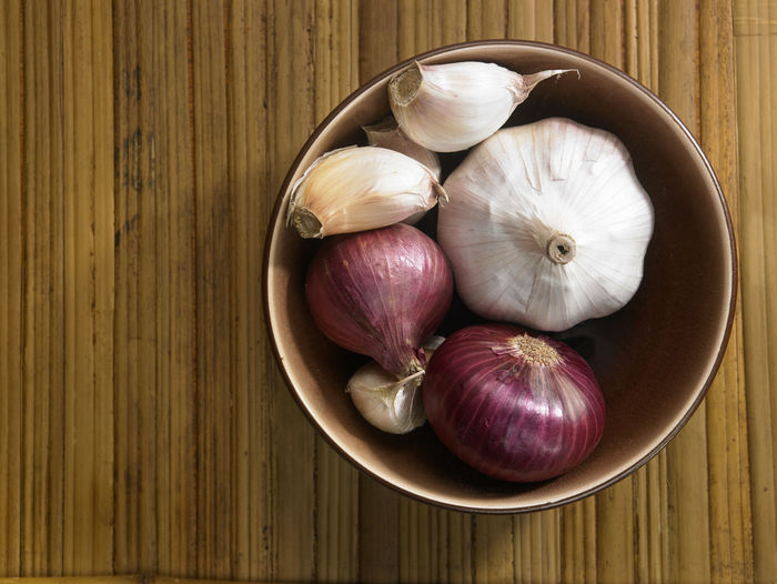 bowl of the onion and garlic Bamboo Background Close-up Food Food And Drink Freshness Garlic Garlic Bulb Healthy Eating High Angle View Indoors  Ingredient No People Onion Raw Food Spice Still Life Table Vegetable Wellbeing Wood - Material