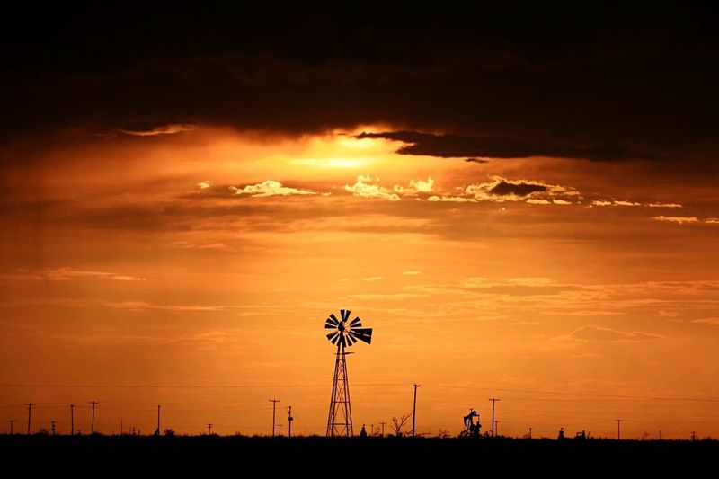 Distant old windmill against dramatic sky at sunset