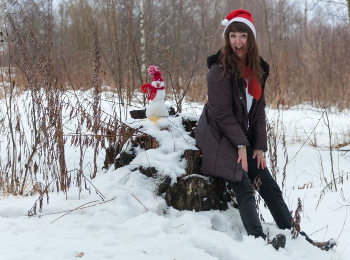 Full Length Portrait Of Woman On Tree Stump At Snow Covered Field