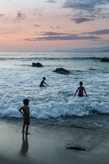 Silhouette children on shore at beach against sky during sunset