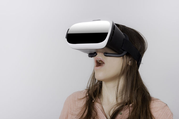 Close-up of woman with virtual reality simulator against wall