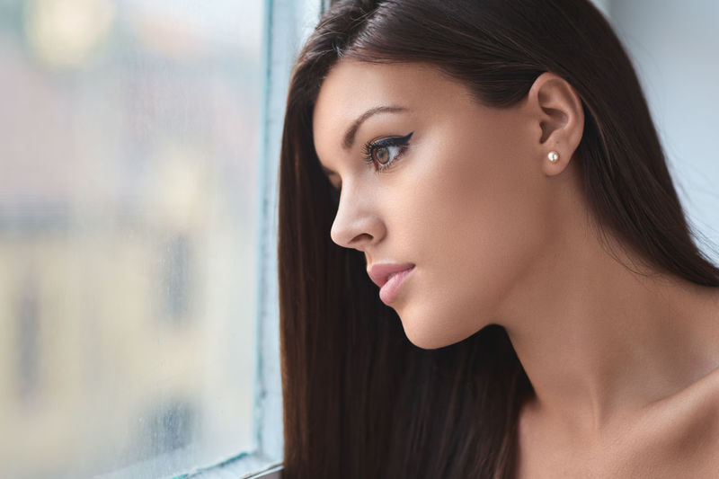 Close-Up Of Young Woman By Window At Home