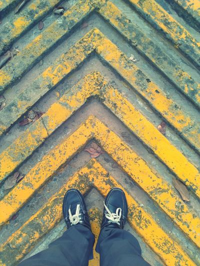 Low section of man standing on patterned footpath