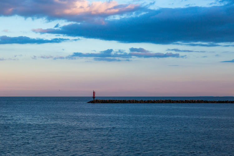 Direction light on sea Beauty In Nature Breakwater Calm Distant Dramatic Sky Help Horizon Horizon Over Water Light House Nautical Vessel Outdoors Protection Queit Relaxing Route Scenics Sea Sky Sunset SUPPORT Tranquility Travel Destinations Water