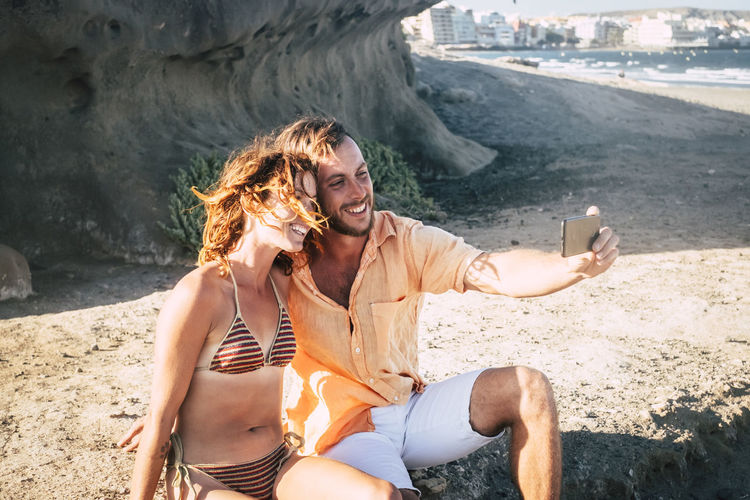 Couple taking selfie with mobile phone at beach