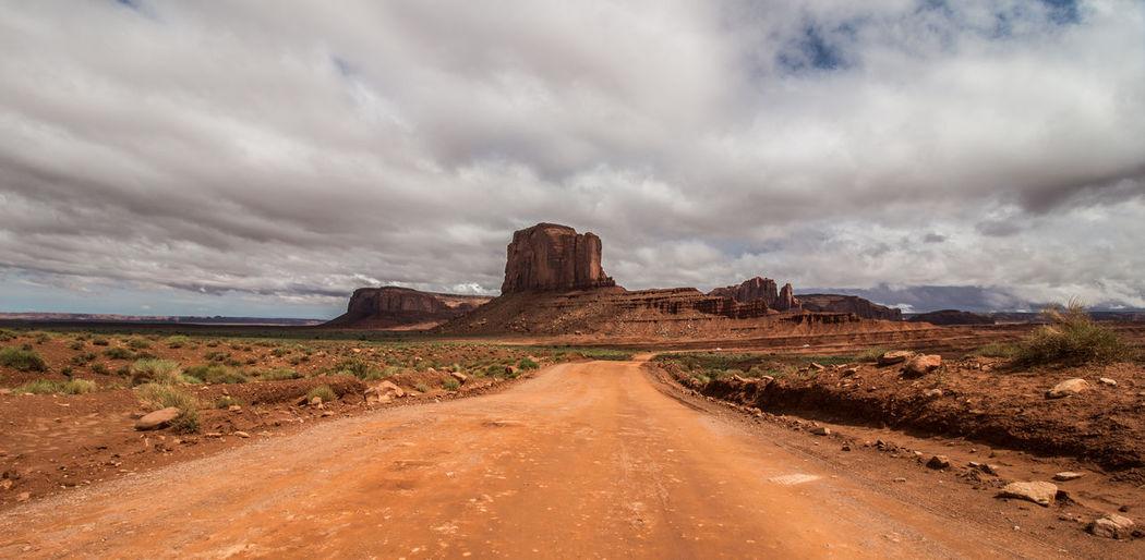 Dirt road on landscape against sky
