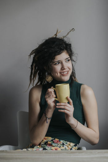 Portrait of a young female model with dreadlocks drinking coffee at home Coffee Happiness Joyful Liquid Millenials Tea Teenagers  Alternative Careless Cup Dreadlocks Drink Food And Drink Front View Happiness Indoors  Joy Lifestyles One Person Portrait Smile Smiling Teenager Teeth Young Women