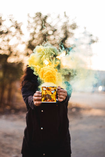 Woman holding mug with yellow emitting smoke against face while standing outdoors