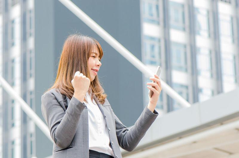 Businesswoman using phone outdoors