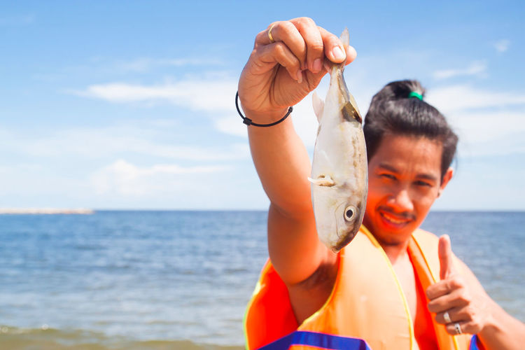 Portrait of man holding fish while gesturing thumbs up against sea