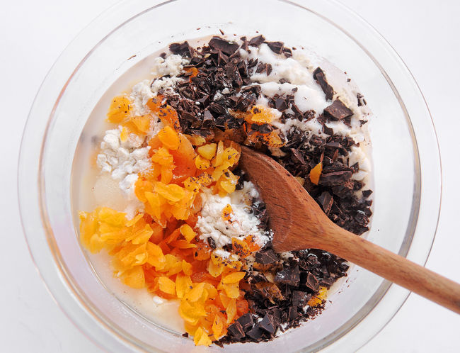 Overhead view of dark chocolate pieces, chopped dried apricots and flour in a glass mixing bowl Dark Chocolate Home Cooking Homemade Food Natural Light Textures Baking Batter Brown Close-up Day Dried Apricots Flour Food Food Prep Glass Bowls Indoors  Mixing Bowl No People Overhead Studio Shot White Wooden Spoon Yellow-orange Color