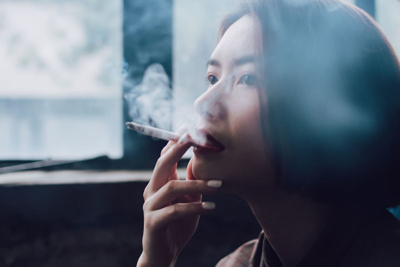 Activity Asian Girl Bad Habit Beautiful Woman Cigarette  Communication Headshot Holding Looking One Person Portrait RISK Smoke - Physical Structure Smoking - Activity Smoking Issues Social Issues Tobacco Product Young Adult