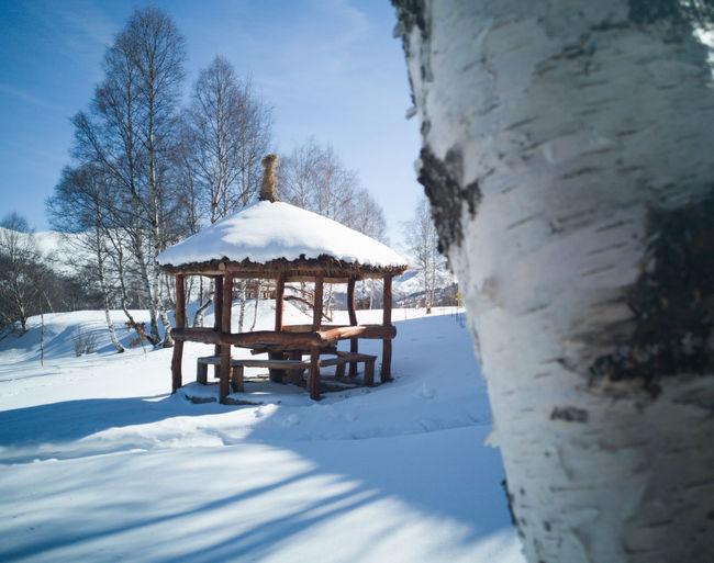 Gazebo on snow covered field against sky