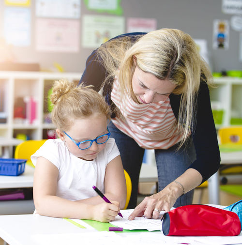 beautiful teacher helps her student to learn Fun Writing Art And Craft Blond Hair Boys Casual Clothing Child Childhood Family Females Girls Hair Hairstyle Holding Indoors  Learn Males  People Real People School Table Teacher Togetherness Two People Women