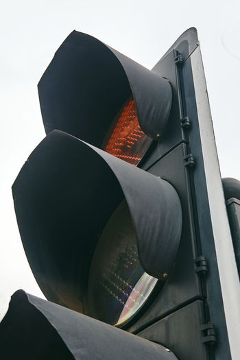 Low angle view of road signal against clear sky