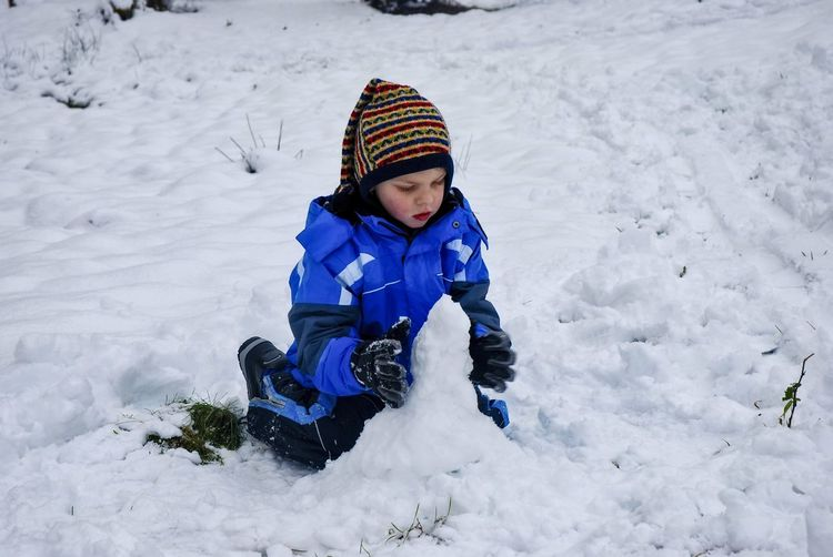 A boy sitting on snow covered land