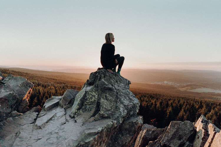 Woman Sitting On Rock Against Landscape