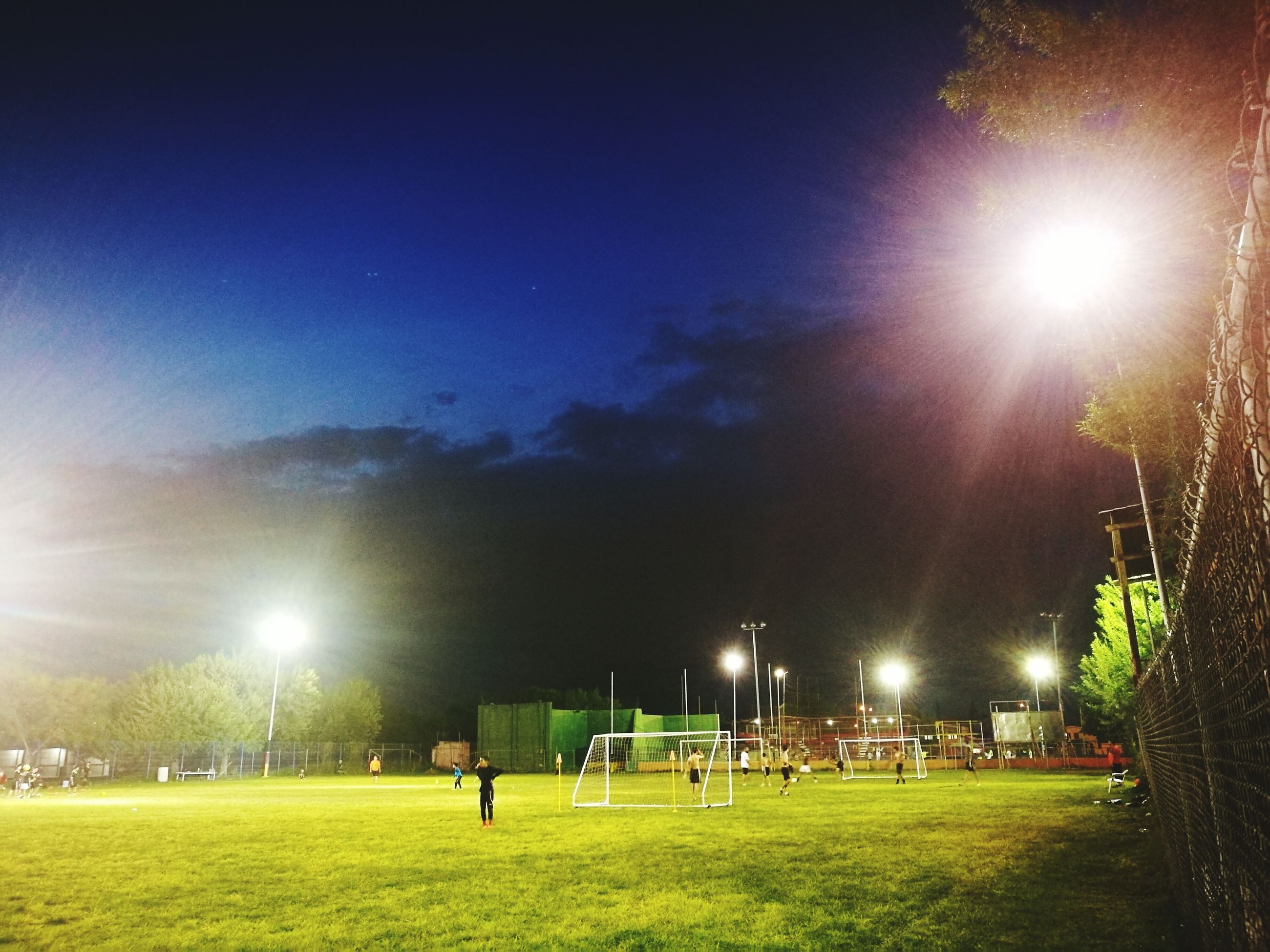 lens flare, illuminated, night, real people, grass, outdoors, floodlight, field, tree, sky, men, soccer field, soccer, sport, nature, playing field, goal post, people