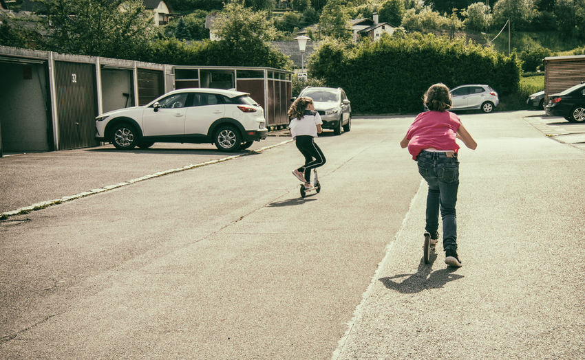 Rear view of children on street against road