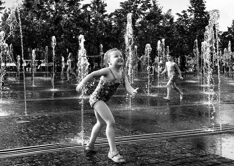 Full length of woman splashing water fountain