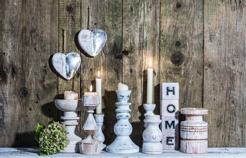 Lit Candles With Christmas Decorations Against Wooden Wall