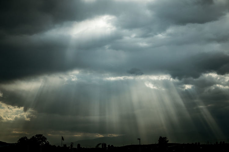 Low angle view of sunlight streaming through storm clouds
