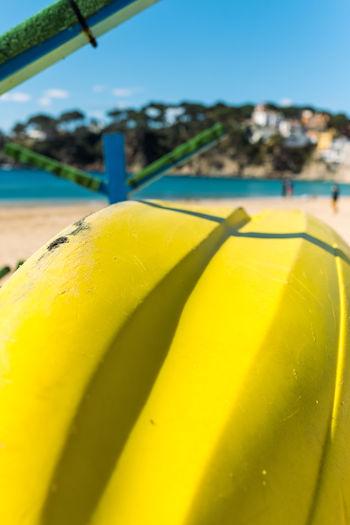 Close-up of yellow umbrella on beach