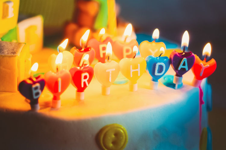 Happy birthday written in lit candles on colorful cake background Birthday Bright Burning Cake Candle Celebrate Colorful Congratulation Dessert Fire Flame Food Fun Happiness Happy Birthday Holiday Light Orange Party Pie Present Surprise Sweet Text Wish Year Yellow