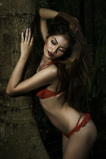 Sensuous woman with arms raised leaning on tree trunk
