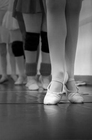 Low Section Of Ballet Dancers Standing On Hardwood Floor