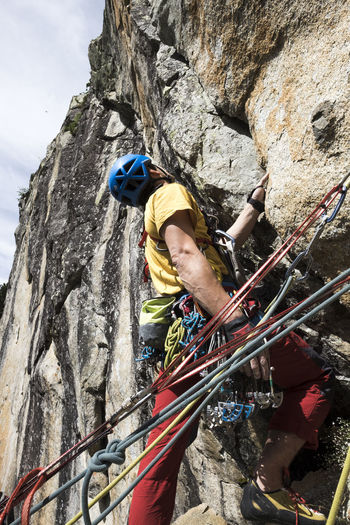 Low angle view of man rock climbing