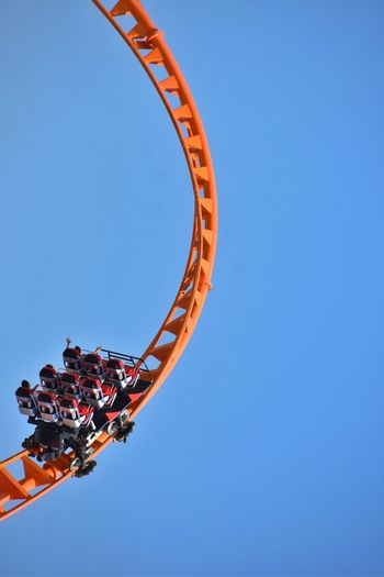 Low angle view of rollercoaster against clear blue sky