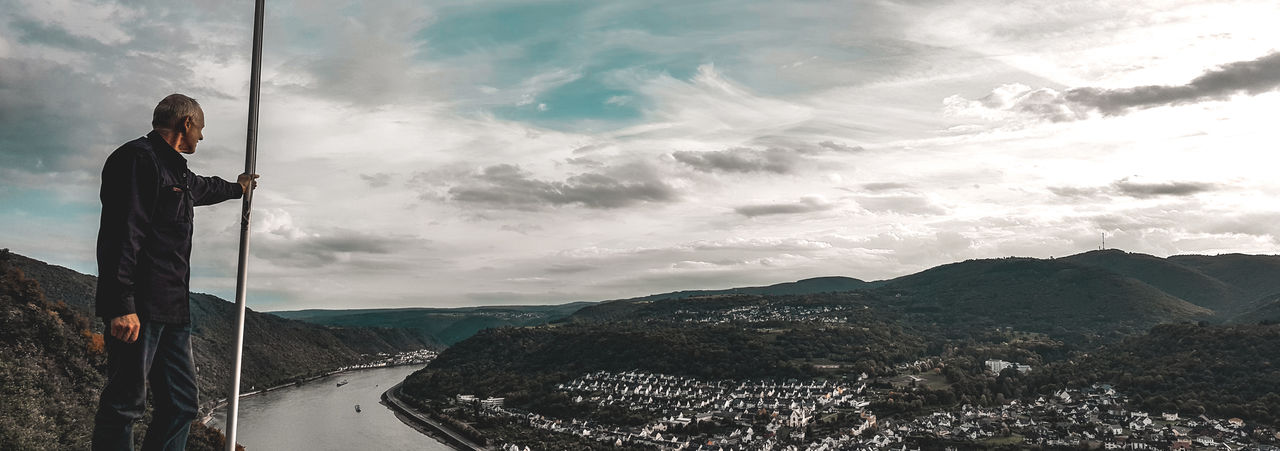 Panoramic Shot Of Man Standing On Mountain By River Against Cloudy Sky