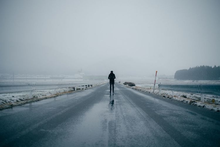 Person Standing On Empty Road Against Sky During Foggy Weather