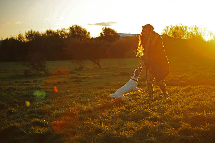 Woman Playing With Dog On Field Against Sky At Sunset