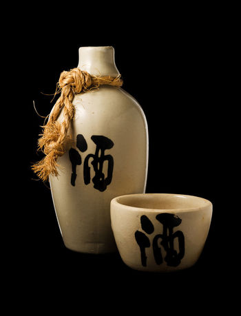 """Sake bottle and cup, with the ideogram for """"liquor"""" on both, isolated on black background with clipping path Beverage Isolated Japan Liquor Porcelain  Sake Alcoholic Drink Black Background Booze Bottle Close-up Container Cut Out Drink Food And Drink Japanese Drink No People Studio Shot"""