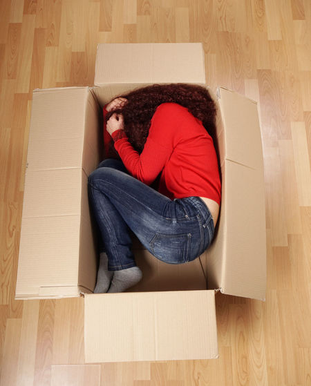 High angle view of woman lying in cardboard box at home