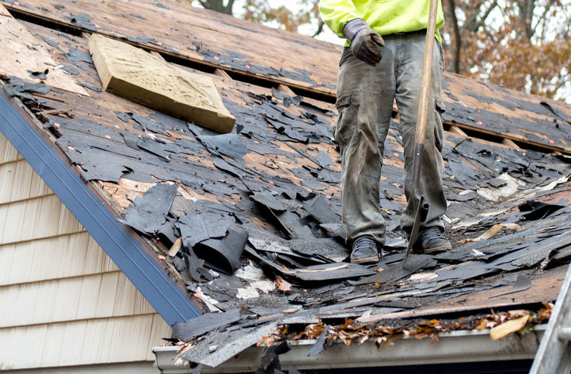 Worker tears off shingles from the roof of an old house