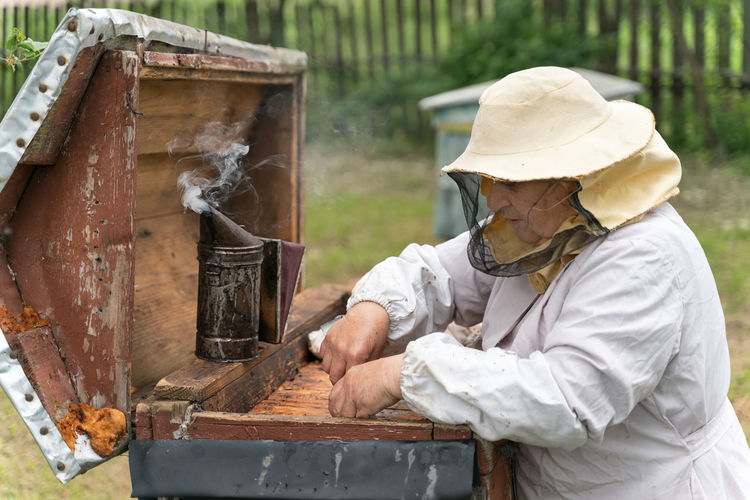 Beekeeper working with smoker at park