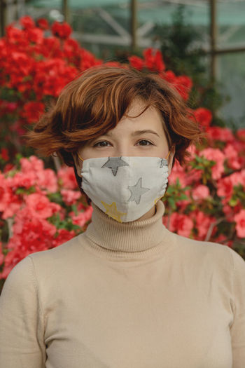 A beautiful woman wearing protective face mask among spring flowers.