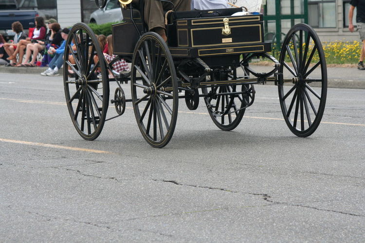Low section of man on motor buggy over street during fourth of july parade