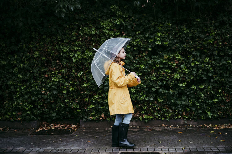 Man with umbrella standing on footpath during rainy season